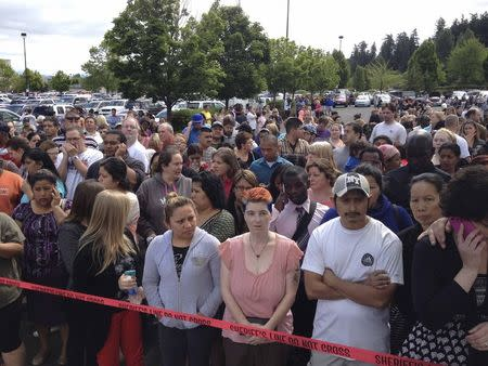 Parents wait behind police tape for students from Reynolds High School to arrive by bus in Troutdale, Oregon
