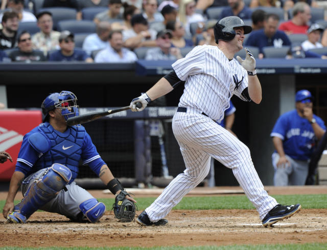 New York Yankees' Brian McCann watches his two-run home run as Toronto Blue Jays catcher Dioner Navarro, left, looks on during the fourth inning of a baseball game Saturday, July 26, 2014, at Yankee Stadium in New York. (AP Photo/Bill Kostroun)