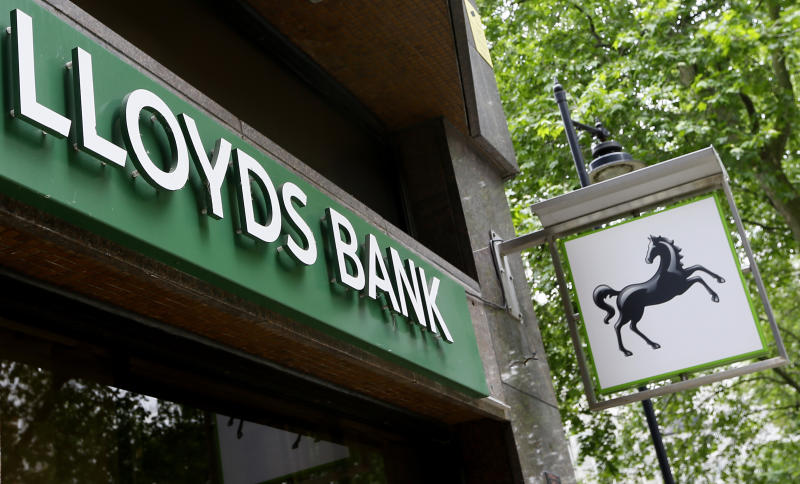 FILE - In this file photo dated Friday, June 5, 2015, The sign showing the Lloyds Bank logo at a branch in London. The lending giant Lloyds on Thursday Feb. 20, 2020, has reported 2019 pre-tax profits of pounds 4.39 billion, down by some 26 per-cent on 2018, after it was hit by a pounds 2.5 billion bill for the payment protection insurance (PPI) scandal. (AP Photo/Kirsty Wigglesworth, FILE)