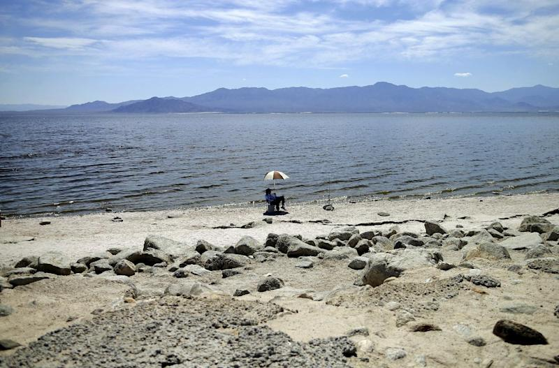 FILE - In this April 30, 2015 file photo, a man fishes for tilapia along the receding banks of the Salton Sea near Bombay Beach, Calif. California officials have proposed spending nearly $400 million over 10 years to slow the shrinkage of the state's largest lake. Gov. Jerry Brown's administration on Thursday, March 16, 2017, unveiled a plan to build ponds on the northern and southern ends of the Salton Sea. It's expected to evaporate at an accelerated pace starting next year when the San Diego region no longer diverts water to the desert region. (AP Photo/Gregory Bull, File)