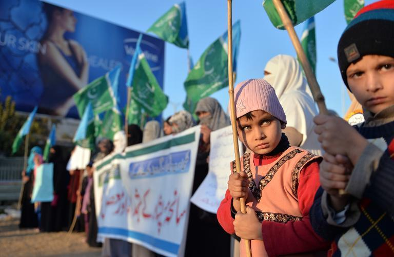 Children hold flags as supporters of Pakistani political and Islamic party Jammat-e-Islami (JI) stage a protest against the Taliban attack on an army-run school in Peshawar, in Islamabad on December 26, 2014