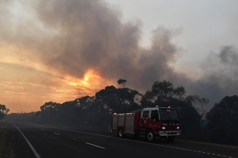 A CFA fire crew is seen along the Princes Highway outside of Bunyip in Victoria, Sunday, March 3, 2019. The fires in Bunyip State Park started after lightning strikes on Friday afternoon, with 300 emergency workers deployed to fight the blazes. (AAP Image/James Ross) NO ARCHIVING