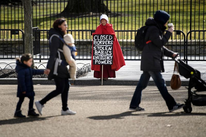 People walk past an activist dressed as a character from the TV show The Handmaid's Tale during a protest against US President Donald Trump immigration policy near the White House Feb. 18, 2019 in Washington, DC. (Photo: Brendan Smialowski/AFP/Getty Images)