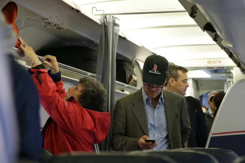 A passenger check his cell phone while boarding a flight, Thursday, Oct. 31, 2013, in Boston. The Federal Aviation Administration issued new guidelines Thursday, under which passengers will be able to use devices to read, work, play games, watch movies and listen to music, from the time they board to the time they leave the plane. (AP Photo/Matt Slocum)