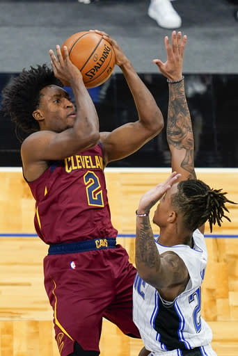 Cleveland Cavaliers guard Collin Sexton (2) makes a shot over Orlando Magic guard Markelle Fultz, right, during the first half of an NBA basketball game, Monday, Jan. 4, 2021, in Orlando, Fla. (AP Photo/John Raoux)