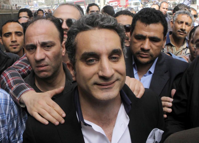 FILE - In this Sunday, March 31, 2013 file photo, a bodyguard secures popular Egyptian television satirist Bassem Youssef, who has come to be known as Egypt's Jon Stewart, as he enters Egypt's state prosecutors office to face accusations of insulting Islam and the country's Islamist leader in Cairo, Egypt. U.S. satirist Jon Stewart appears Friday, June 21, 2013 on a talk show with Bassem Youssef, known as Egypt's Jon Stewart(AP Photo/Amr Nabil, File)