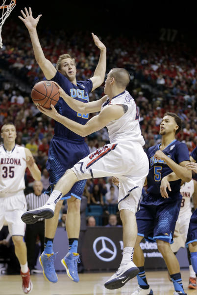 Arizona's T.J. McConnell passes off the ball against UCLA's David Wear in the first half during the championship game of the NCAA Pac-12 conference college basketball tournament, Saturday, March 15, 2014, in Las Vegas. (AP Photo/Julie Jacobson)