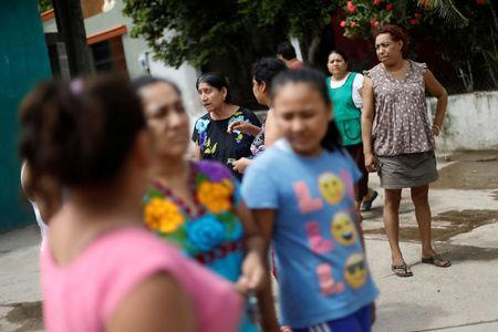 Felina, 50, an indigenous Zapotec transgender woman also know as Muxe, speaks with her neighbors outside her house destroyed after an earthquake that struck on the southern coast of Mexico late on Thursday, in Juchitan, Mexico, September 10, 2017. REUTERS/Edgard Garrido