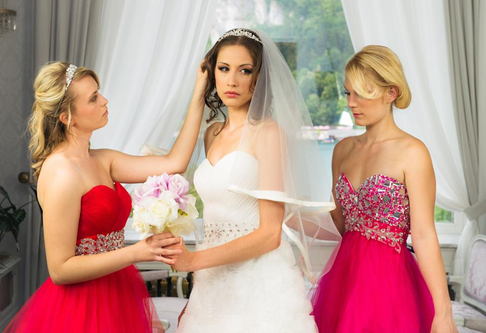 Two bridesmaids helping an angry bride