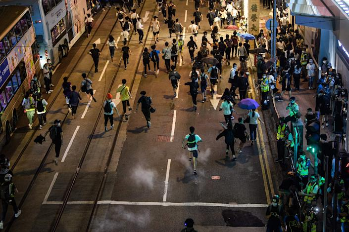 Pro-democracy protesters run as police fire pepper ball rounds to disperse the crowd in the Central district of Hong Kong on June 9, 2020, as the city marks the one-year anniversary since pro-democracy protests erupted | ANTHONY WALLACE/AFP via Getty Images