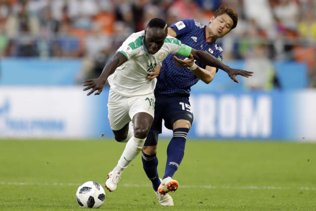 Senegal's Ismaila Sarr, left, and Japan's Hiroki Sakai fight for the ball during the group H match between Japan and Senegal at the 2018 soccer World Cup at the Yekaterinburg Arena in Yekaterinburg , Russia, Sunday, June 24, 2018. (AP Photo/Natacha Pisarenko)