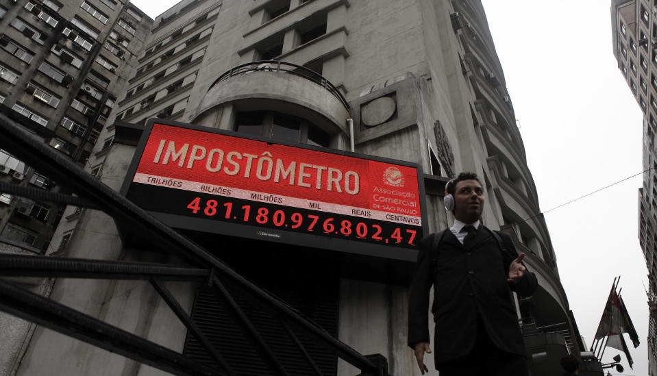 A man stands in front of the Impostometro (Taxometer), which displays the amount of taxes paid by citizens of Brazil, in downtown Sao Paulo city, April 27, 2012. The Federal Revenue Service, which has gained global renown for its tough and creative tactics, will be one of the most important keys to Brazil's economic prospects in 2012. President Dilma Rousseff is counting on the agency's tax-collecting prowess to help her government meet ambitious budget targets without smothering the country's suddenly brittle economy. To match Feature BRAZIL-TAXES/ Picture taken April 27, 2012. REUTERS/Nacho Doce (BRAZIL - Tags: POLITICS BUSINESS)