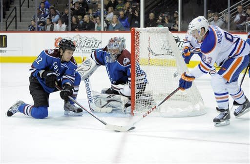 Colorado Avalanche defenseman Matt Hunwick (22) blocks a shot by Edmonton Oilers center Ryan Nugent-Hopkins (93) as Colorado Avalanche goalie Semyon Varlamov (1) from Russia looks on during the second period of an NHL hockey game on Saturday, March 10, 2012, in Denver. (AP Photo/ Jack Dempsey)