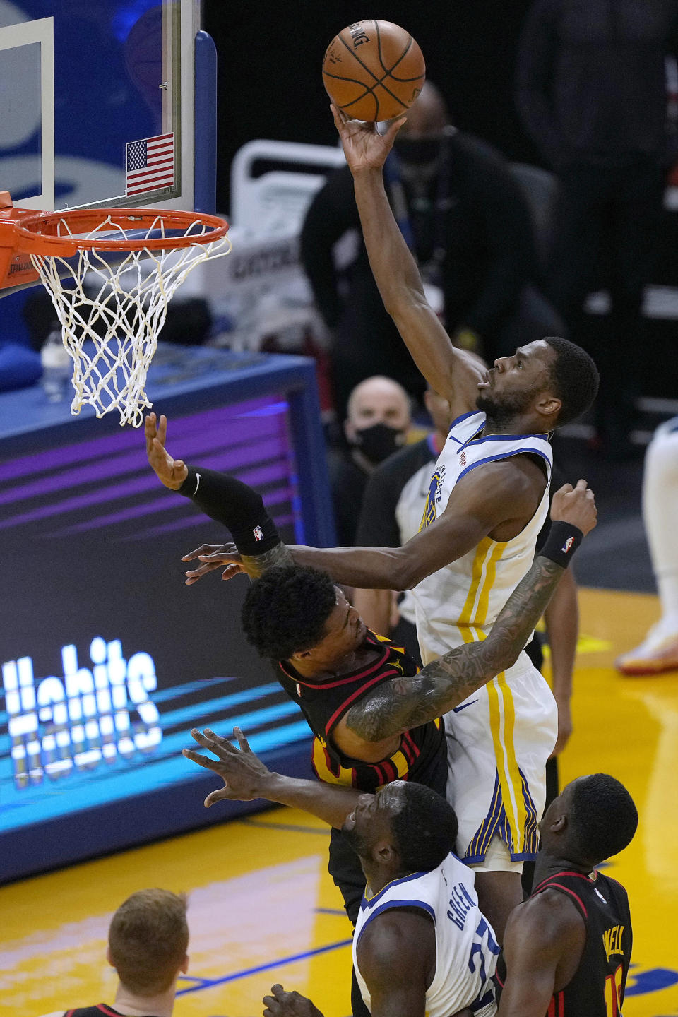 Golden State Warriors forward Andrew Wiggins (22) drives to the basket against Atlanta Hawks forward John Collins (20) during the first half of an NBA basketball game in San Francisco, Friday, March 26, 2021. (AP Photo/Tony Avelar)