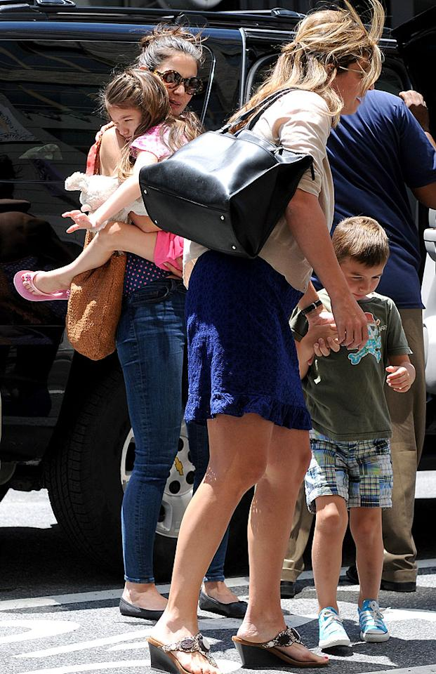On July 5, Katie and Suri had a fun-filled day, which started with a visit to Children's Museum of the Arts in SoHo. When the gals arrived, Suri, who was wearing pink and toting a plush toy, had her legs wrapped around her mom as they entered the building with a few other young friends. Katie sported a backless halter top, skinny jeans, and a messy bun for the outing.