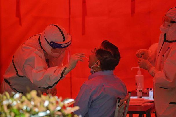 PHOTO: A medical worker takes a swab sample from a man to test for COVID-19 in Wuhan in China's central Hubei province on May 19, 2020. (Hector Retamal/AFP via Getty Images)