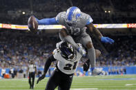Detroit Lions running back D'Andre Swift (32) tries to jump over the tackle of Baltimore Ravens cornerback Brandon Stephens (21) in the second half of an NFL football game in Detroit, Sunday, Sept. 26, 2021. (AP Photo/Tony Ding)