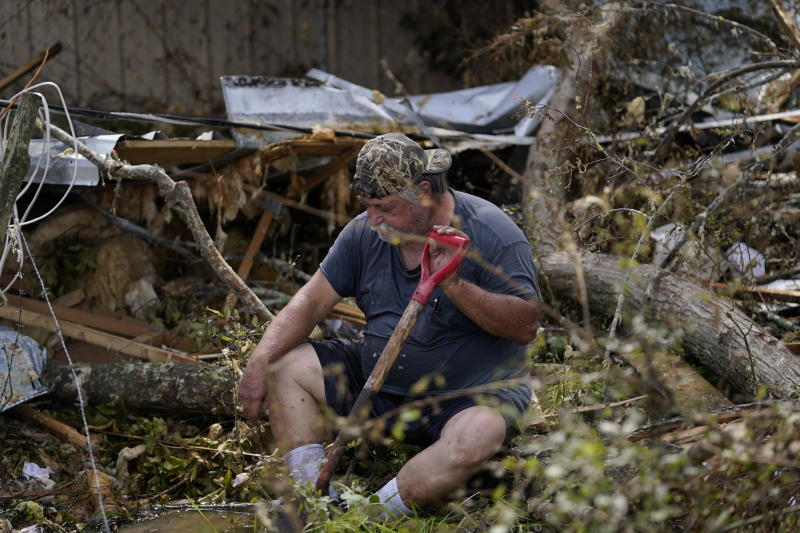 Bradley Beard rests as he searches in vain for his water shutoff valve, next to his heavily damaged home and the destroyed trailer home of his daughter Nicole, in Hackberry, La., in the aftermath of Hurricane Laura, Saturday, Aug. 29, 2020. (AP Photo/Gerald Herbert)