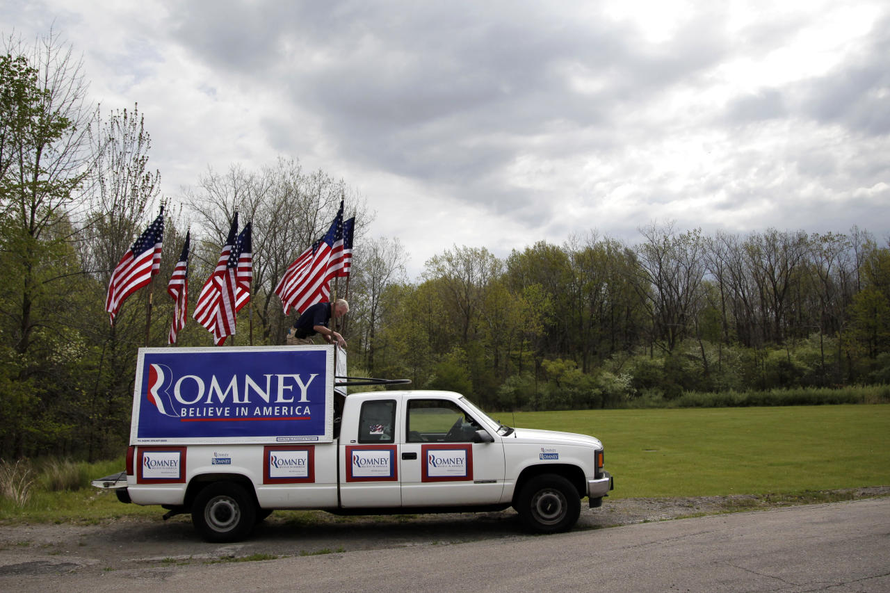 Jim Wilson, 69, of Buckingham, Va., hangs a sign for Republican presidential candidate, former Massachusetts Gov. Mitt Romney at a campaign rally in Lorain, Ohio, Thursday, April 19, 2012. (AP Photo/Jae C. Hong)