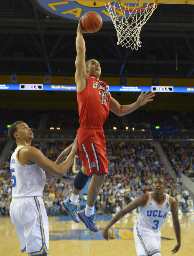 Arizona guard Nick Johnson, center, goes up to dunk as UCLA forward Kyle Anderson, left, and guard Jordan Adams defend during the second half of an NCAA college basketball game on Thursday, Jan. 9, 2014, in Los Angeles. (AP Photo/Mark J. Terrill)