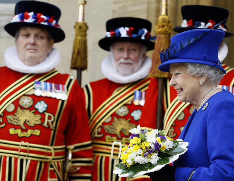 Britain's Queen Elizabeth II smiles as she walks past Yeoman of the Guard, after attending the Maundy service, at Christ Church Cathedral in Oxford, England, Thursday, March 28, 2013. During the service the Queen distributed the Maundy money to 87 women and 87 men, one for each of The Queen's 87 years. Each recipient receives two purses, one red and one white. The red purse will contain a 5 pound coin and 50 pence coin commemorating the 60th anniversary of The Queen's Coronation. The white purse will contain uniquely minted Maundy Money. This takes the form of silver one, two, three and four penny pieces, the sum of which equals the number of years the Monarch has years of age. This year there will be 87 pennies worth distributed. (AP Photo/Kirsty Wigglesworth, Pool)