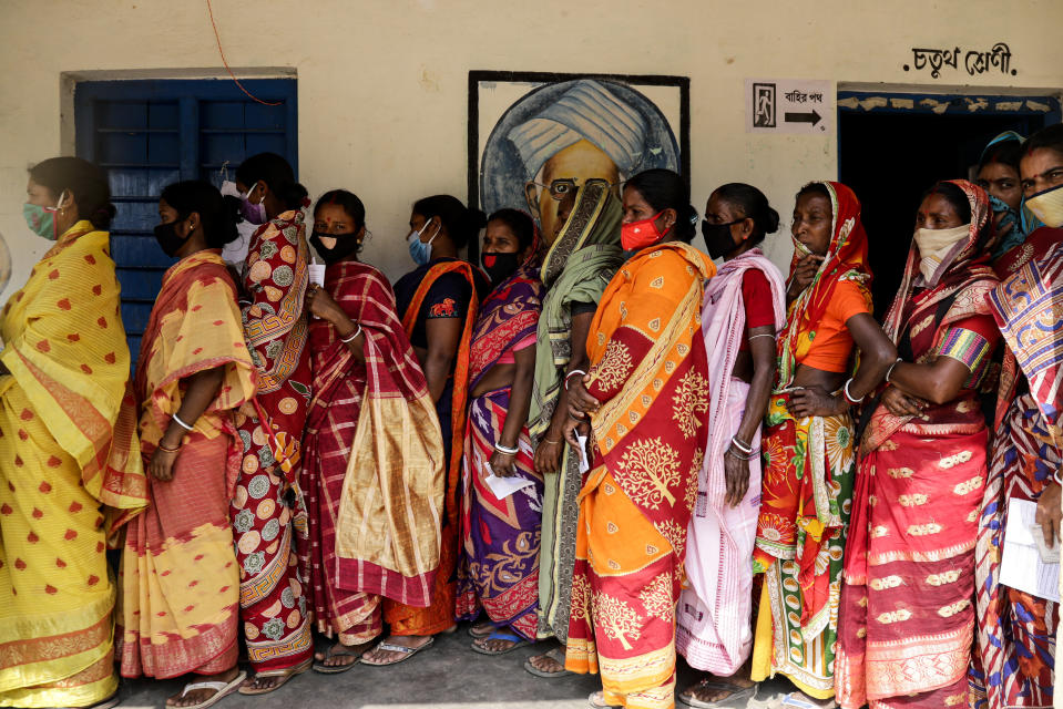 Voters stand in a queue to cast their votes during the first phase of elections in West Bengal state in Pirakata, India, Saturday, March 27, 2021. Voting began Saturday in two key Indian states with sizeable minority Muslim populations posing a tough test for Prime Minister Narendra Modi's popularity amid a months-long farmers' protest and the economy plunging with millions of people losing jobs because of the coronavirus pandemic. (AP Photo/Bikas Das)