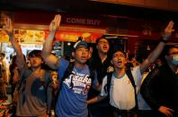 """FILE PHOTO: Pro-democracy protesters chant slogans as they imitate a three-finger salute from movie """"The Hunger Games"""" during a confrontation with the police at Mongkok shopping district in Hong Kong"""