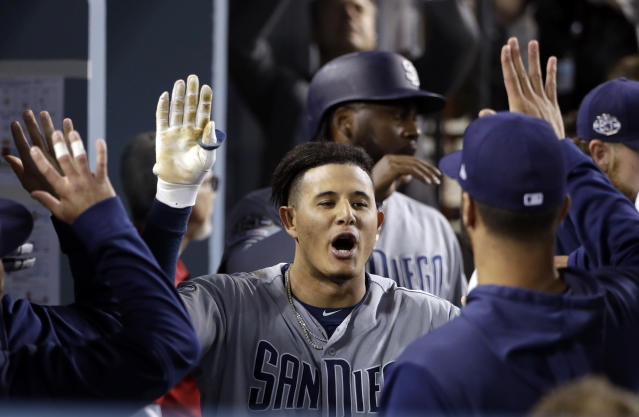 San Diego Padres' Manny Machado, center, celebrates his two-run home run with teammates in the dugout during the fourth inning of a baseball game against the Los Angeles Dodgers on Tuesday, May 14, 2019, in Los Angeles. (AP Photo/Marcio Jose Sanchez)
