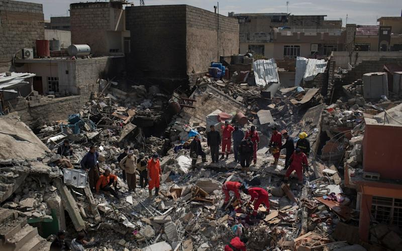 Civil protection rescue teams work on the debris of a house destroyed by an airstrike during fighting between Iraqi security forces and Islamic State militants in Mosul in March - AP