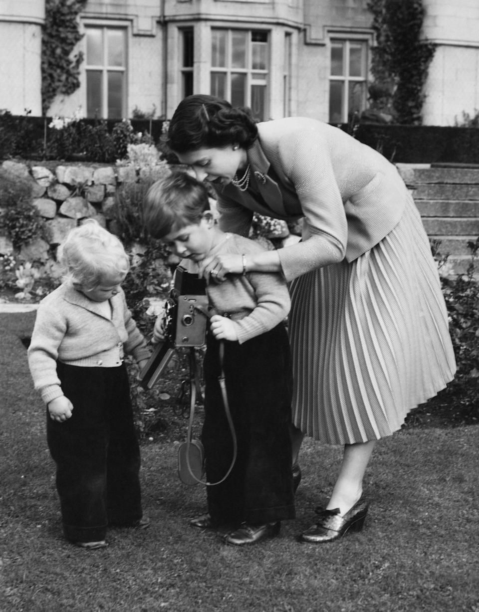 Queen Elizabeth II helps Prince Charles take a picture of his sister, Princess Anne, in Balmoral, Scotland, in 1952. (Photo: Lisa Sheridan via Getty Images)