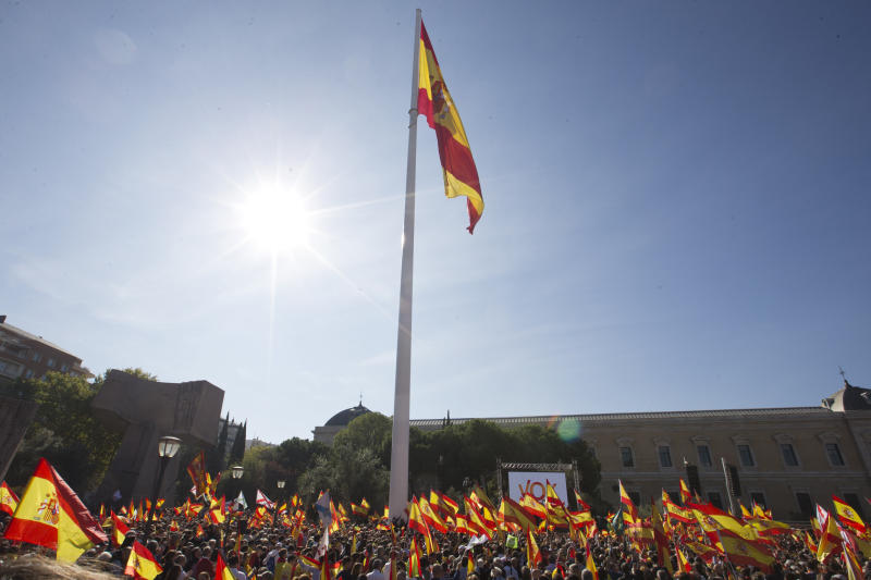 A big Spanish flag flutters as other wave smaller Spanish flags during for a rally to promote 'Spanish Unity' during a rally by the right wing VOX party in Madrid, Spain, Saturday, Oct. 26, 2019. The VOX rally comes 2 days after the exhumation and reburial of Spanish dictator Gen. Francisco Franco from the grandiose Valley of the Fallen mausoleum outside Madrid to their new resting place at the Mingorrubio cemetery, 57 kilometers (35 miles) away. (AP Photo/Paul White)