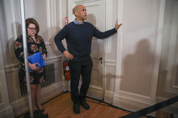 U.S. Sen. Cory Booker, D-N.J., waits on the sidelines for his turn to speak at a post-midterm election victory celebration in Manchester, N.H., on Saturday, Dec. 8, 2018. (AP Photo/Cheryl Senter)
