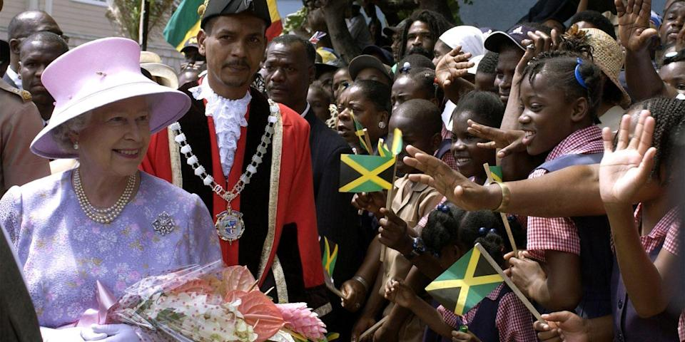 <p>In a purple floral printed dress and pink hat for a royal visit to Montego Bay, Jamaica, the queen looked thrilled to meet an enthusiastic group of school children.</p>