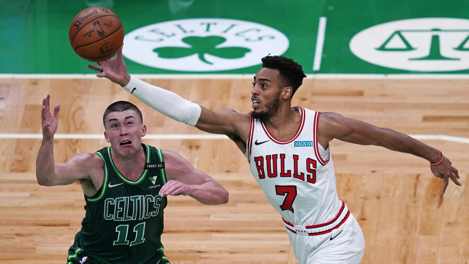 Chicago Bulls forward Troy Brown Jr., left, grabs a rebound over Boston Celtics guard Payton Pritchard, right, during the first half of an NBA basketball game, Monday, April 19, 2021, in Boston. (AP Photo/Charles Krupa)