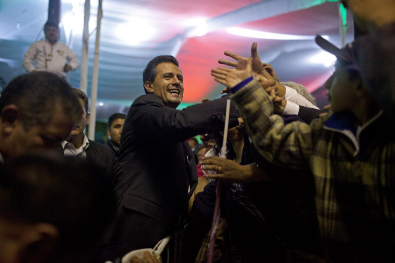 Enrique Pena Nieto, presidential candidate for the Revolutionary Institutional Party (PRI), center, greets supporters at the party's headquarters in Mexico City, early Monday July 2, 2012. Mexico's old guard sailed back into power after a 12-year hiatus Sunday as the official preliminary vote count handed a victory to Pena Nieto, whose party was long accused of ruling the country through corruption and patronage. (AP Photo/Alexandre Meneghini)