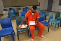 Immigration detainee Alexander Martinez takes out his paperwork during an interview with The Associated Press inside the Winn Correctional Center in Winnfield, La., Friday, July 30, 2021. (AP Photo/Gerald Herbert)