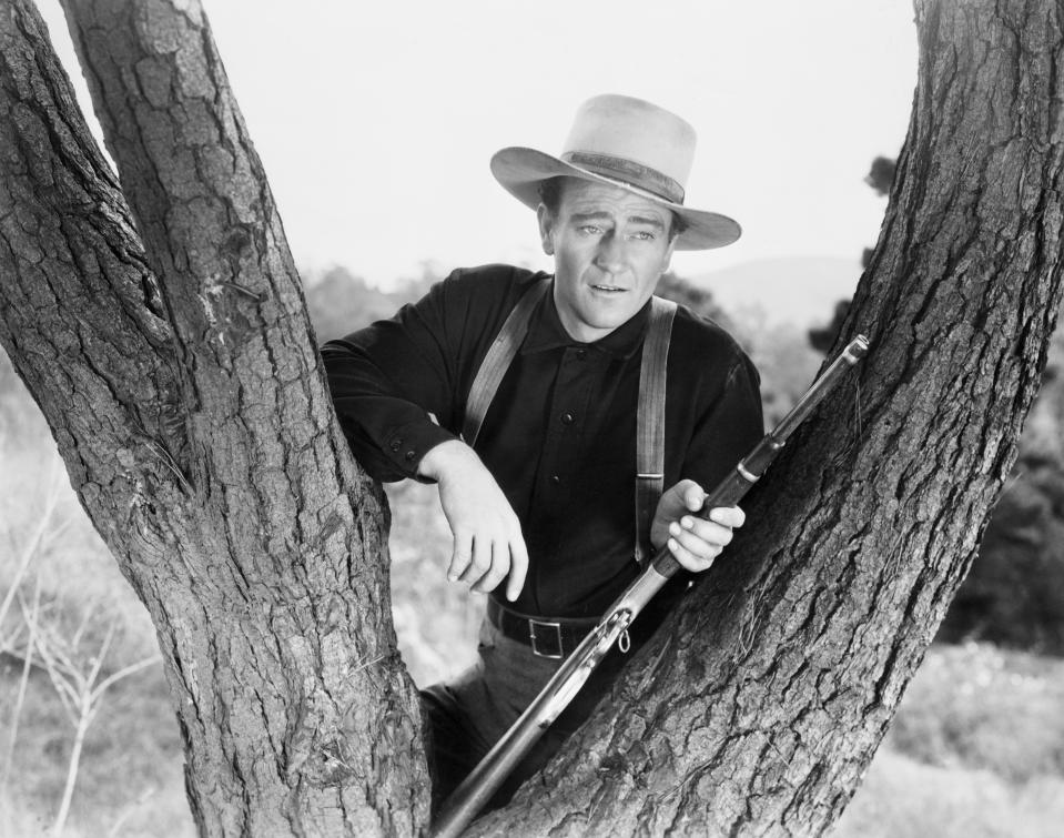 """(Original Caption) 1940-John Wayne as he appeared in the film """"Shepherd of the Hills: resting his rifle in the fork of a tree. Photograph, 1940. Movie Still. Movie released in 1941. (Photo by AS400 DB/Bettmann Archive)"""