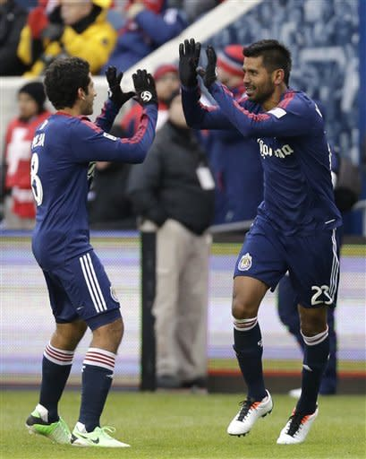 Chivas USA defender Joaquin Velazquez, right, celebrates with midfielder Edgar Mejia after scoring his goal against the Chicago Fire during the second half of an MLS soccer match in Bridgeview, Ill., Sunday March 24, 2013. Chivas USA won 4-1. (AP Photo/Nam Y. Huh)
