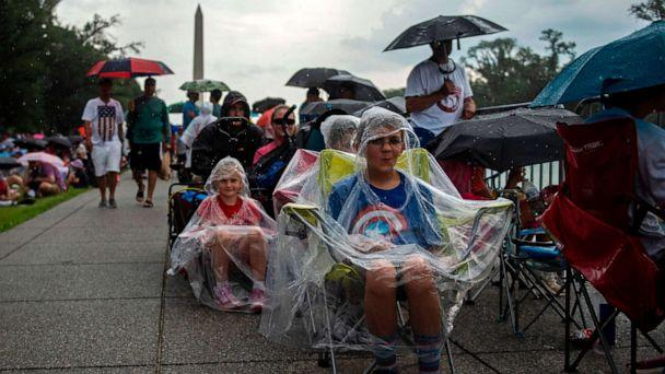 PHOTO: People cover from the rain as they gather on the National Mall ahead of the 'Salute to America' Fourth of July event with President Donald Trump at the Lincoln Memorial in Washington, July 4, 2019. (Andrew Caballero-reynolds/AFP/Getty Images)