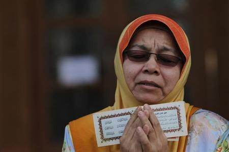 A Muslim woman recites a prayer during a demonstration outside Malaysia's Court of Appeal in Putrajaya