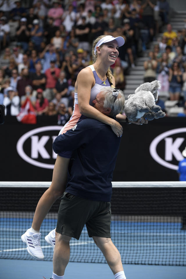 Denmark's Caroline Wozniacki is lifted by her coach and father Piotr after her third round loss to Tunisia's Ons Jabeur at the Australian Open tennis championship in Melbourne, Australia, Friday, Jan. 24, 2020. (AP Photo/Andy Brownbill)