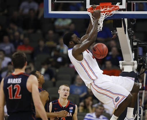 Florida's Patric Young dunks against Virginia's Joe Harris (12), Darion Atkins and Paul Jesperson (2) in the first half of their NCAA tournament second-round college basketball game at CenturyLink Center in Omaha, Neb., Friday, March 16, 2012. (AP Photo/Nati Harnik)