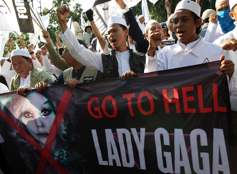 Muslim men shout slogans during a rally against U.S. pop singer Lady Gaga's concert that is scheduled to be held on June 3, outside the U.S. Embassy in Jakarta, Indonesia, Friday, May 25, 2012. Lady Gaga might have to cancel her sold-out show in Indonesia because police worry her sexy clothes and dance moves undermine Islamic values and will corrupt the country's youth. (AP Photo/Dita Alangkara)