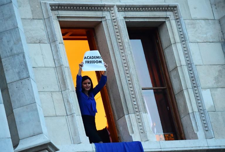 Member of Parliament Agnes Kunhalmi of the Hungarian Socialist Party displays an EU flag at the window of an office room in the parliament building as protesters gather below on April 4, 2017