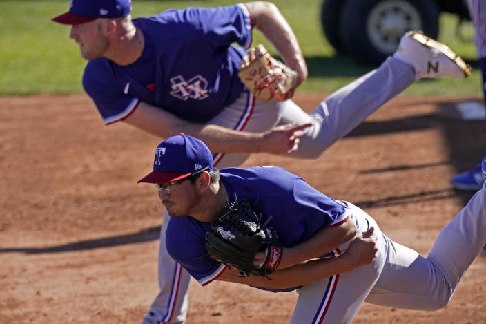 Texas Rangers pitchers Kyle Cody, top and Dane Dunning throw during spring training baseball practice Monday, Feb. 22, 2021, in Surprise, Ariz. (AP Photo/Charlie Riedel)