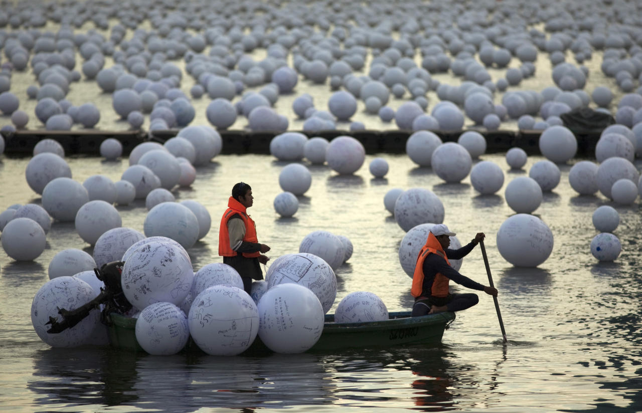 "Workers arrange ""wishing spheres"" as part of an art installation on the Singapore River December 18, 2009. People pen their New Year wishes on these spheres throughout December to be placed on the river as part of the coming New Year Day celebrations. REUTERS/Edgar Su (SINGAPORE - Tags: SOCIETY)"