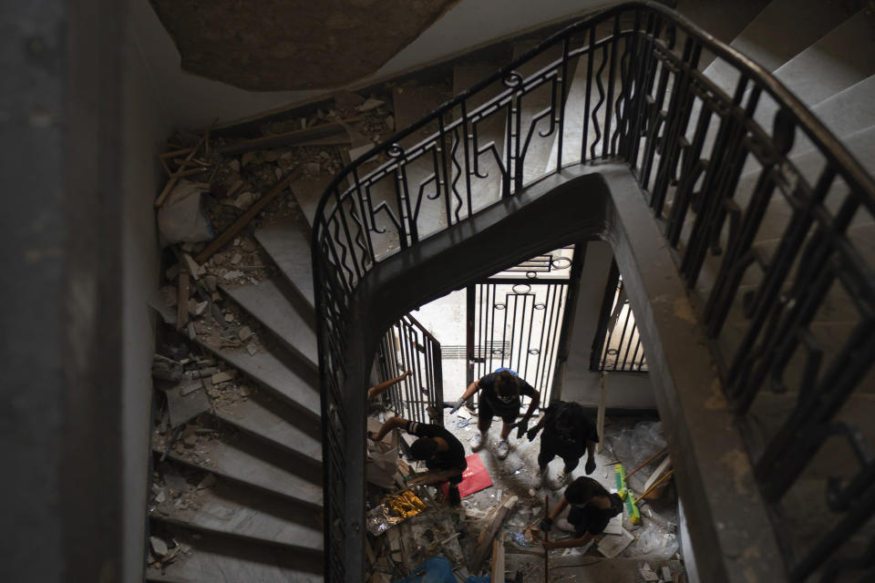 People remove debris of a damaged building at a neighborhood near the scene of Tuesday's explosion that hit the seaport of Beirut, Lebanon, Friday, Aug. 7, 2020. Rescue teams were still searching the rubble of Beirut's port for bodies on Friday, nearly three days after a massive explosion sent a wave of destruction through Lebanon's capital. (AP Photo/Felipe Dana)