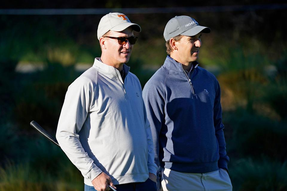 FILE - In this Feb. 6, 2020 file photo, Peyton Manning, left, and his brother Eli Manning wait to hit from the first tee of the Spyglass Hill Golf Course during the first round of the AT&T Pebble Beach National Pro-Am golf tournament in Pebble Beach, Calif.