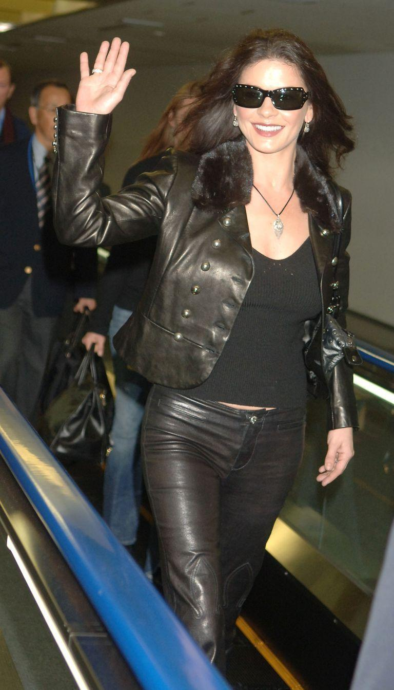 <p>Catherine Zeta-Jones greets fans with a warm smile and a wave as she rides a moving walkway at the Narita International Airport on a visit to Japan in 2006. </p>