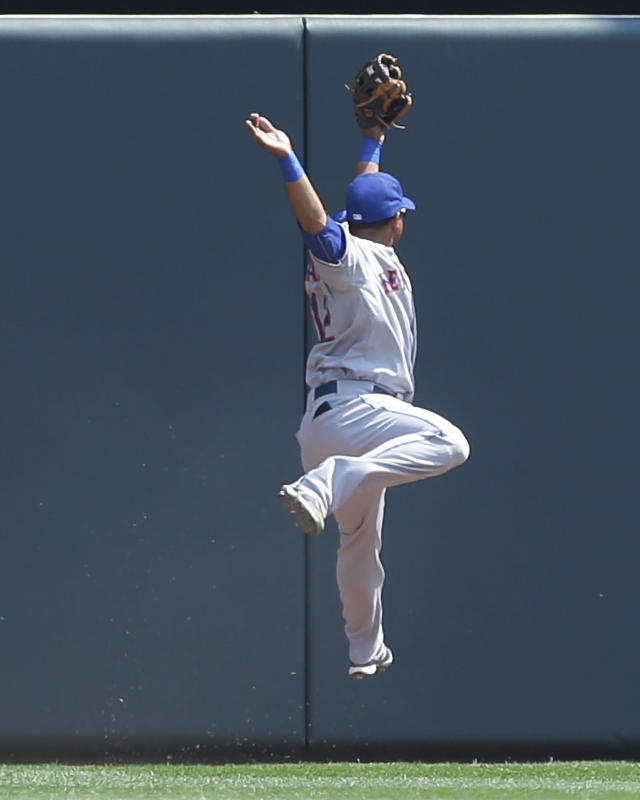 New York Mets center fielder Juan Lagares pulls in a deep fly ball off the bat of Minnesota Twins' Josh Willingham before crashing into the wall in the first inning of a baseball game, Monday, Aug. 19, 2013 in Minneapolis. (AP Photo/Jim Mone)